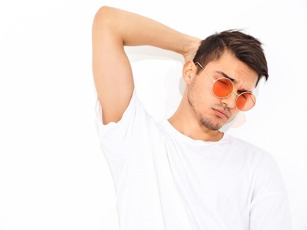Retrato de homem jovem bonito modelo vestido com roupas jeans e camiseta posando de óculos de sol. tocando sua cabeça