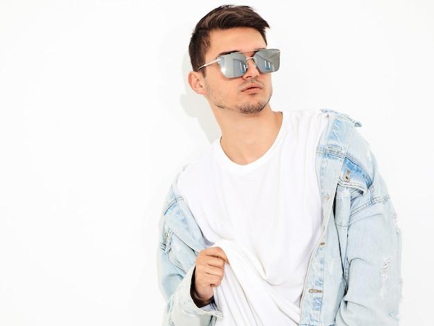 Retrato de homem jovem bonito modelo vestido com roupas jeans em posando de óculos de sol. isolado