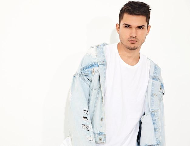 Retrato de homem jovem bonito modelo vestido com roupas jeans posando. isolado