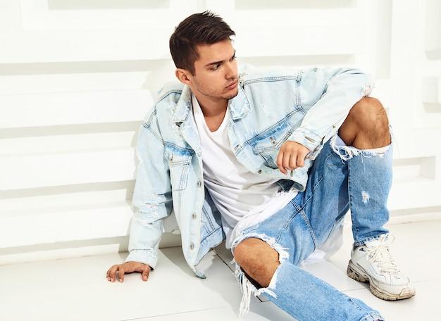 Retrato de homem jovem bonito modelo vestido com roupas jeans, sentado perto da parede texturizada branca