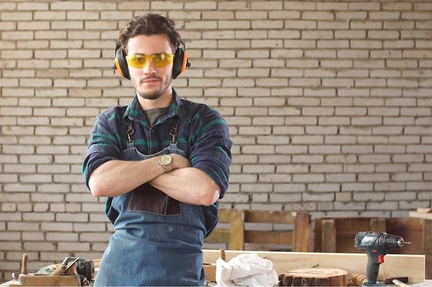 Retrato de homem jovem carpinteiro cruzando os braços e olhando para a câmera