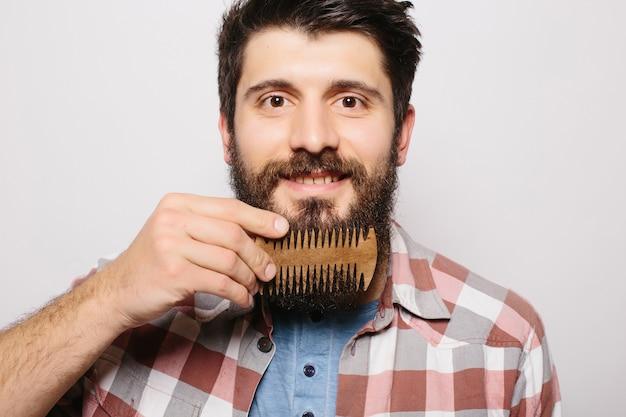 Retrato de homem jovem e atraente ruiva hipster com olhar sério e confiante, segurando o pente de madeira e fazendo sua barba espessa. barbeiro barbudo elegante em camisa xadrez penteando no salão. horizontal