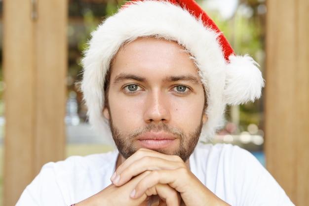 Retrato de homem jovem e bonito hippie com barba por fazer e sorriso confiante, posando dentro de casa, com as mãos cruzadas, usando um chapéu de papai noel vermelho com pelo branco