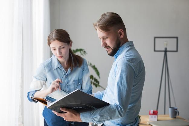 Retrato, de, homem jovem, e, mulher olha, catálogo interior, em, escritório