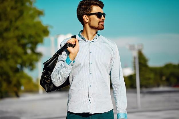 Retrato de homem jovem elegante confiante feliz modelo bonito em pano hipster com saco na rua, estilo de vida