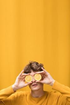 Retrato, de, homem jovem, em, um, cena amarela, com, fatias limão, frente, olhos