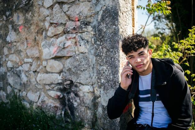 Retrato, de, homem jovem, falando, ligado, cellphone, perto, parede pedra