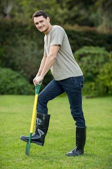 Retrato, de, homem jovem, ficar, com, um, ancinho ajardinando, em, jardim