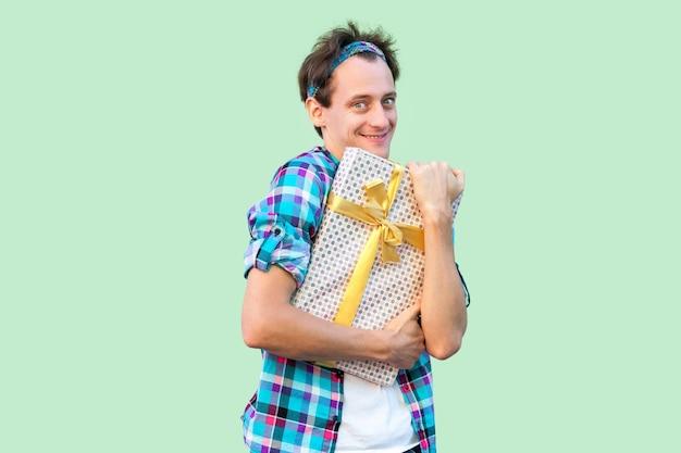 Retrato de homem jovem hippie de prazer em t-shirt branca e camisa quadriculada em pé e abraçando o presente com laço amarelo, sorriso malicioso, olhando para a câmera. interior, isolado, foto de estúdio, fundo verde