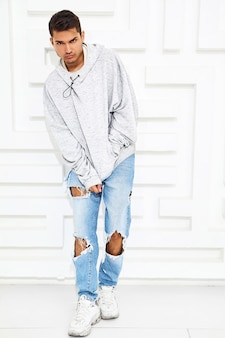 Retrato de homem jovem modelo bonito, vestido com roupas de capuz casual cinza posando perto de parede branca texturizada
