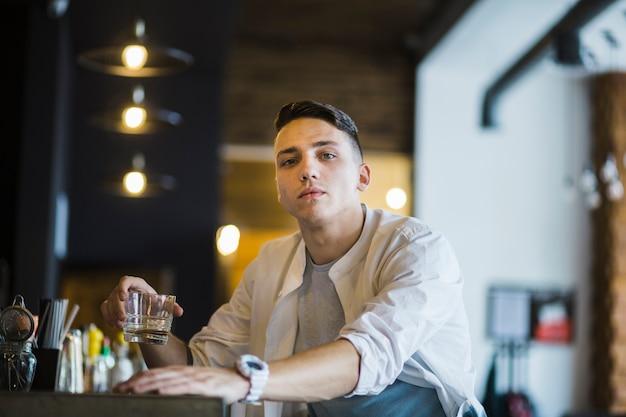 Retrato, de, homem jovem, segurando, copo, de, uísque