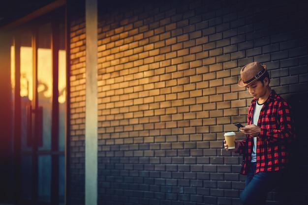 Retrato, de, homem jovem, segurando telefone móvel, e, xícara, de, um, café