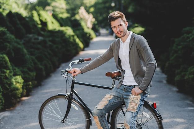 Retrato, de, homem jovem, sentando, ligado, bicicleta