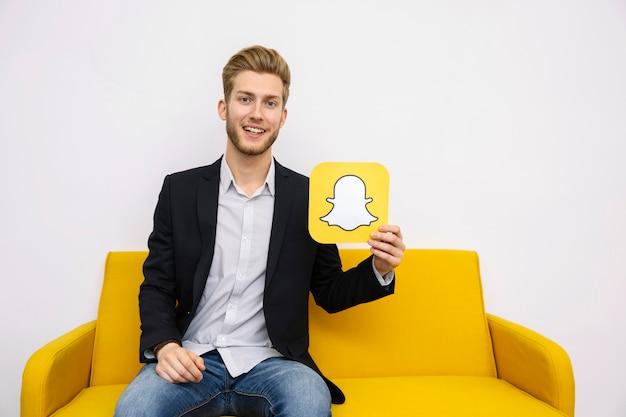 Retrato, de, homem jovem, sentar sofá amarelo, segurando, snapchat, ícone