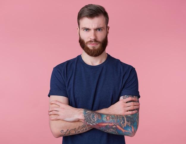 Retrato de homem jovem severo bonito de barba vermelha com braços cruzados, parece indignado, carrancudo e olhando para a câmera isolada sobre fundo rosa.