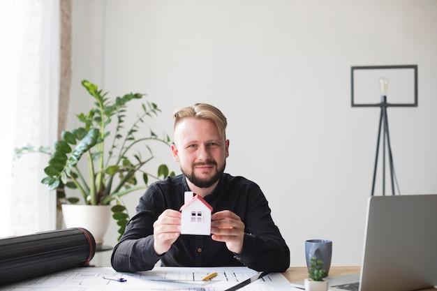 Retrato, de, homem jovem sorridente, segurando, modelo casa, sentando, em, escritório, olhando câmera