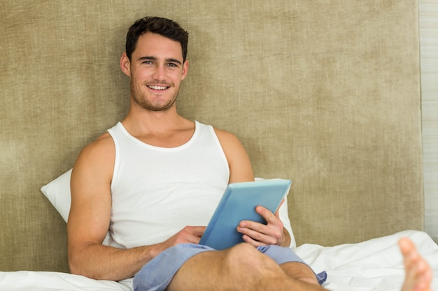 Retrato, de, homem jovem, sorrindo, enquanto, usando, um, tablete digital, em, quarto