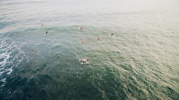Retrato de homem jovem surf na praia com uma prancha de surf. praia de balian