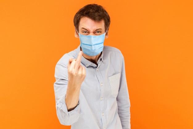 Retrato de homem jovem trabalhador bravo com máscara médica cirúrgica em pé olhando para a câmera com o dedo médio e rosto agressivo. estúdio interno tiro isolado em fundo laranja.