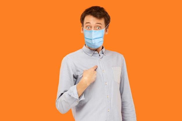 Retrato de homem jovem trabalhador chocado com máscara médica cirúrgica em pé, apontando a si mesmo, perguntando e olhando para a câmera com cara de espanto. estúdio interno tiro isolado em fundo laranja.