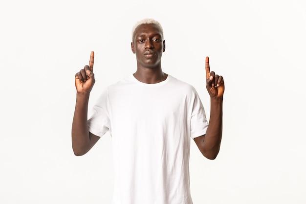 Retrato de homem loiro afro-americano sério e assertivo, parecendo confiante e apontando o dedo para cima