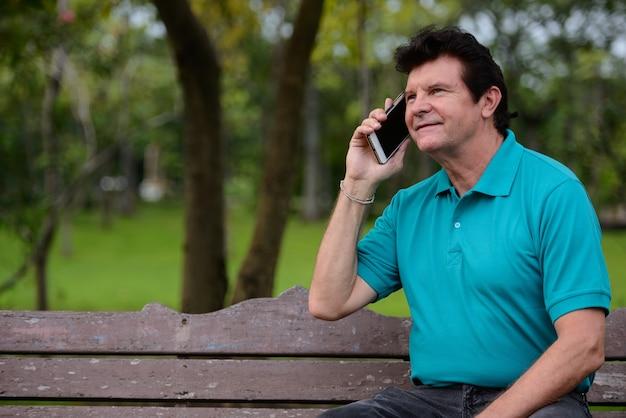 Retrato de homem maduro bonito falando ao telefone no parque