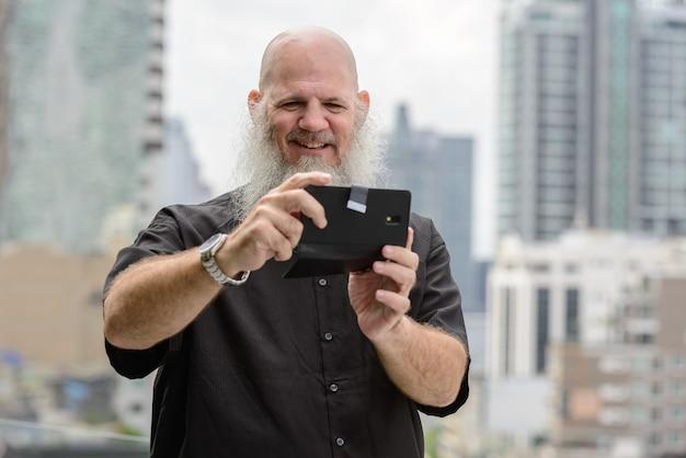 Retrato de homem maduro careca com barba comprida contra a vista da cidade ao ar livre