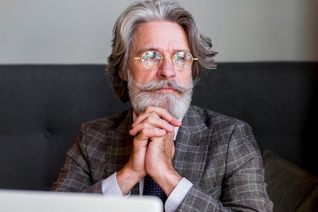 Retrato de homem maduro com óculos pensando