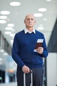 Retrato de homem maduro com passagens e bagagem olhando em pé no aeroporto