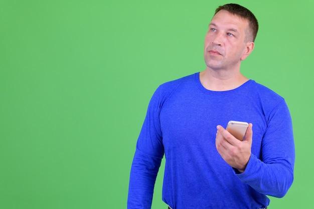 Retrato de homem maduro contra croma key com parede verde