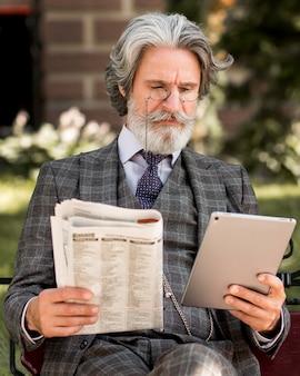 Retrato de homem maduro elegante segurando tablet e jornal