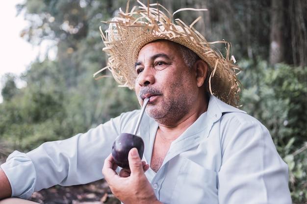Retrato de homem maduro, estilo rural bebendo a infusão típica da argentina e do uruguai chamada mate.