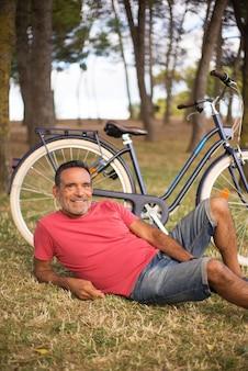 Retrato de homem maduro feliz descansando em uma bicicleta