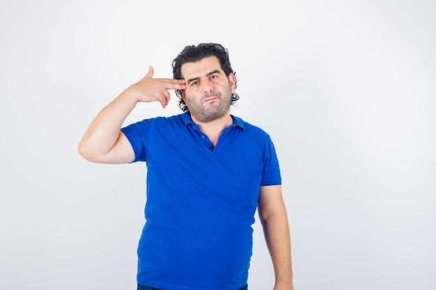 Retrato de homem maduro mostrando gesto de suicídio em camiseta azul e olhando pensativo para a frente