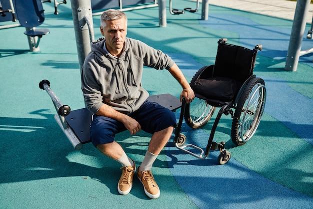Retrato de homem maduro, olhando para a câmera enquanto está sentado no banco perto da cadeira de rodas que ele está se recuperando.