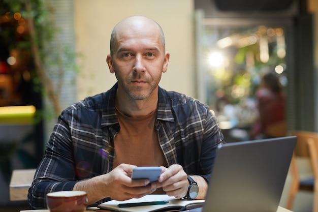 Retrato de homem maduro usando telefone celular e olhando enquanto está sentado à mesa em frente ao laptop no café