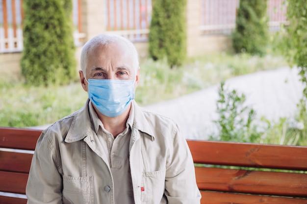 Retrato de homem maduro, vestindo uma máscara protetora, andando na cidade. o rosto de imagem de um jovem vestindo uma máscara para evitar germes, fumaça tóxica e poeira.