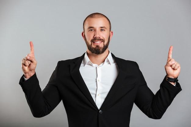 Retrato de homem masculino sorridente no terno de negócio posando na câmera e apontando os dedos para cima no espaço da cópia, isolado sobre a parede cinza
