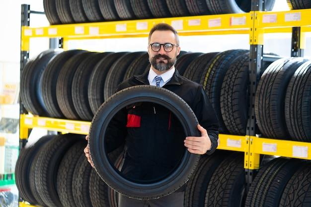 Retrato de homem mecânico com pneus de carro na estação de serviço. mecânico masculino segurando pneu de carro em loja de automóveis