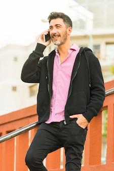Retrato, de, homem moderno, com, seu, passe bolso, falar telefone móvel