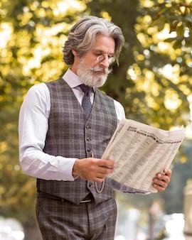 Retrato de homem moderno lendo jornal