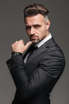 Retrato de homem morena rico 30 anos de terno preto, posando com elegante relógio no pulso, isolado sobre grafite