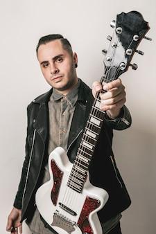 Retrato de homem mostrando guitarra elétrica