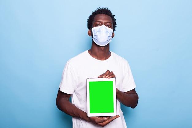 Retrato de homem mostrando tela verde vertical em tablet digital