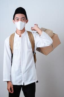 Retrato de homem muçulmano asiático contra cinza vestindo roupas muçulmanas e segurando uma caixa de presentes com uma mochila