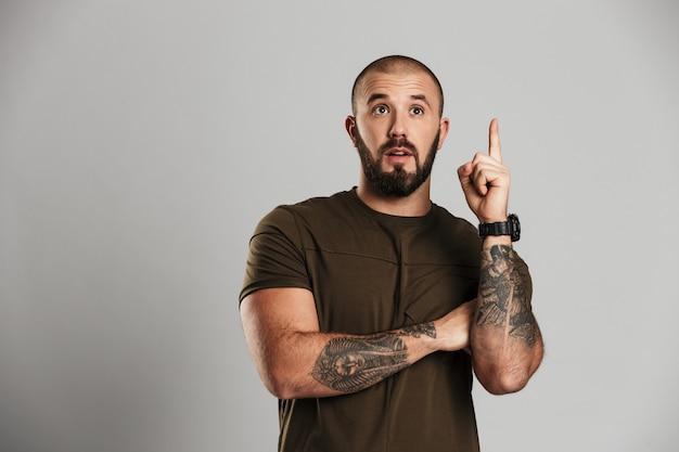 Retrato de homem musculoso animado com barba e bigode aparecendo dedo, expressando uma nova idéia, isolada sobre parede cinza
