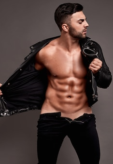 Retrato de homem musculoso bonito em jaqueta de couro na parede cinza