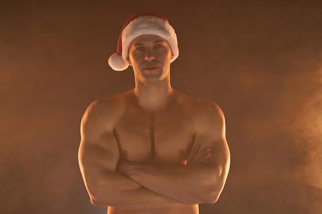 Retrato de homem musculoso com chapéu de papai noel de natal, mãos postas e sorriso no fundo esfumaçado macho stripper de torso nu, sem camisa