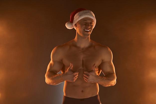 Retrato de homem musculoso com chapéu de papai noel de natal, mostrando o polegar e o sorriso no fundo esfumaçado macho shirtless nu torso stripper cara de papai noel sexy quente homem sedutor para as férias