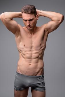 Retrato de homem musculoso e bonito sem camisa cinza